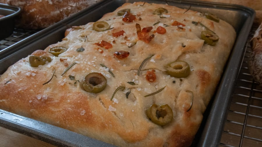 rectangle cooked bread topped with olives, rosemary, salt and sundried tomatoes