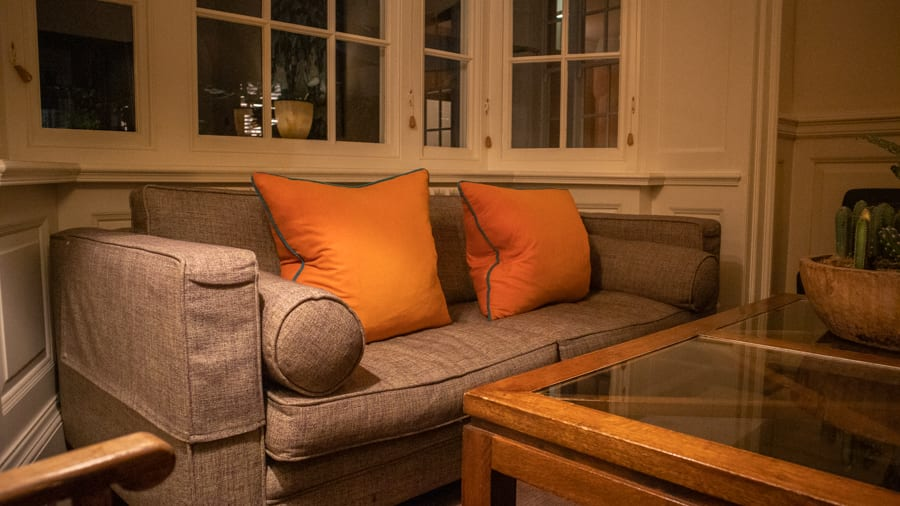 grey sofa with two orange square cushions piped in grey underneath windows with a glass topped table in front