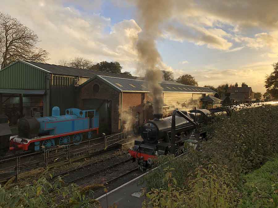 railway yard with a black steam train in front and a blue steam train coming out of a shed beside it