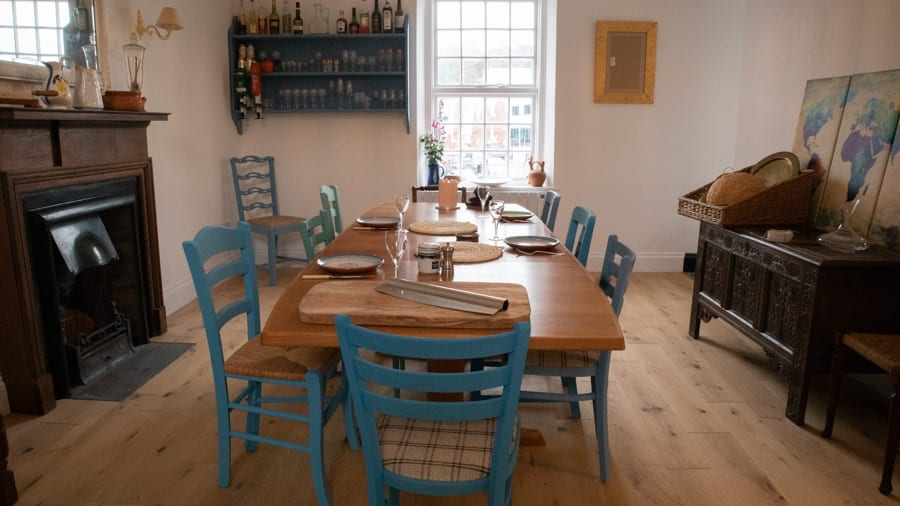 wooden table with blue painted chairs . There is a fireplace on the left and a low unit with a cane dome on top.