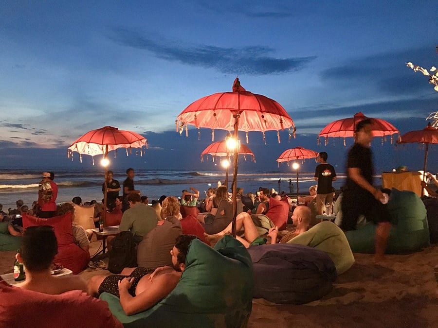 people relaxing on beanbags on Seminyak beach in the evening under red umbrellas