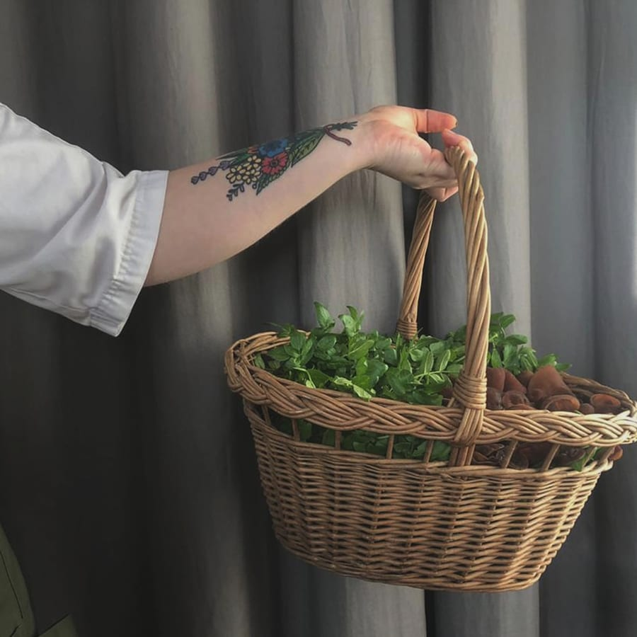 woman's arm with tattoo holding a basket of vegetables