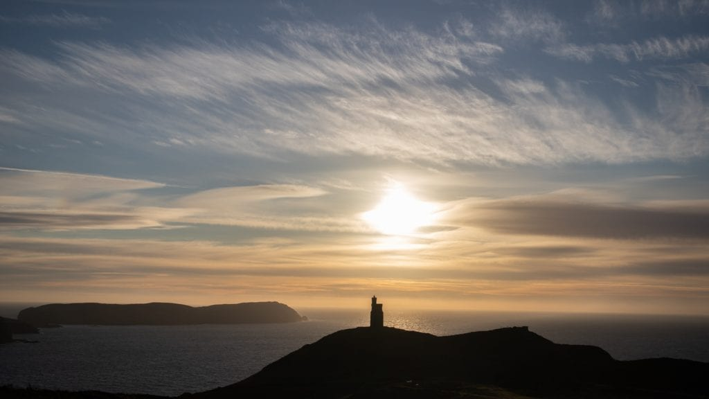 silhouette of a tower on at hill overlooking the sea with the setting sun and clouds in the sky