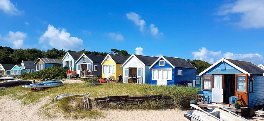 A row of different painted beach huts with grass and sand in front