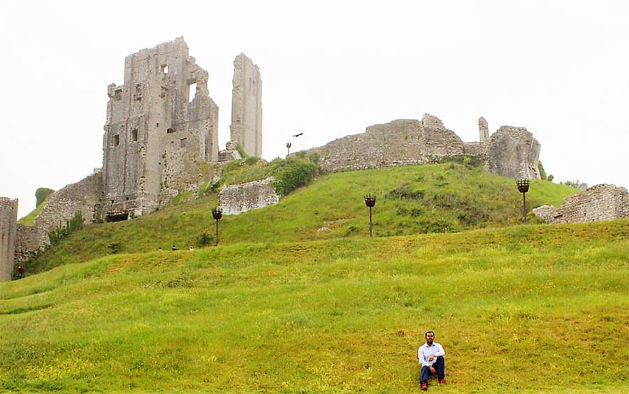 Ruins of Corfe Castle with green sloping grass lawns