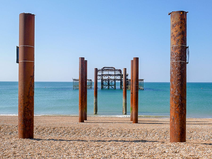 pairs of rusting iron posts leading into the sea