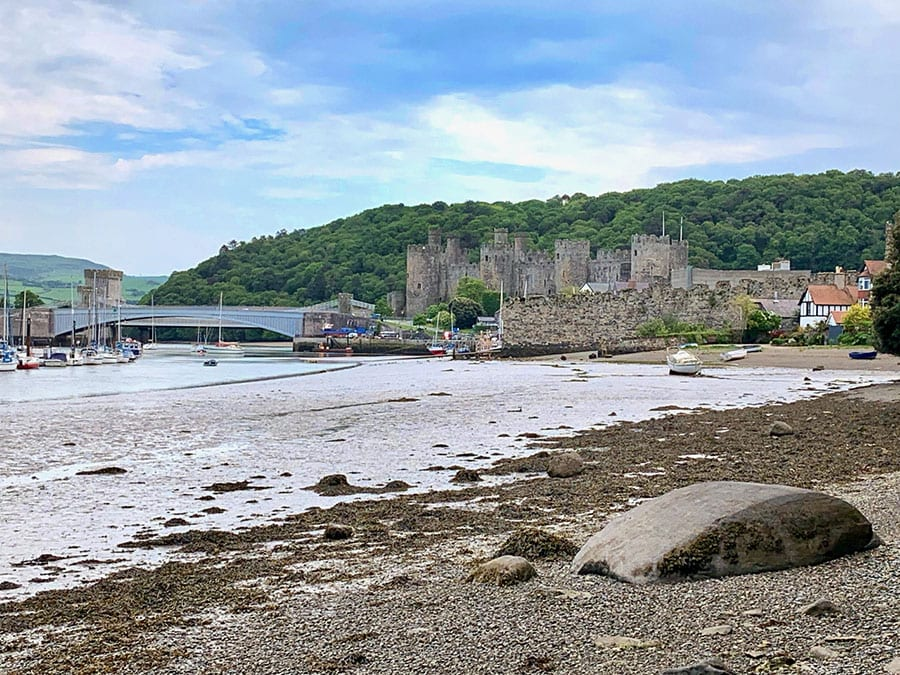 pebble beach with Castle Conwy in the background with a bridge over the river