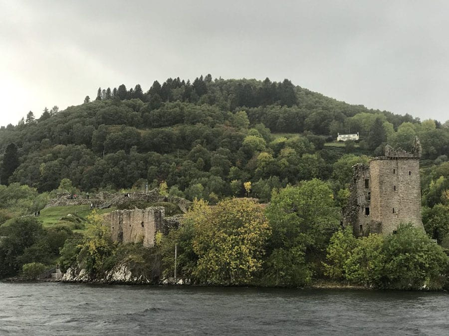 Green wooded hill with the ruins of Urquhart Castle at the bottom on the banks of the Loch Ness