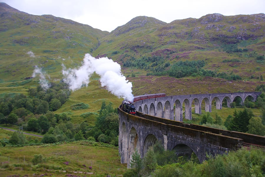 Black and red steam train on a curved viaduct with a series of arches below, green hills in the background