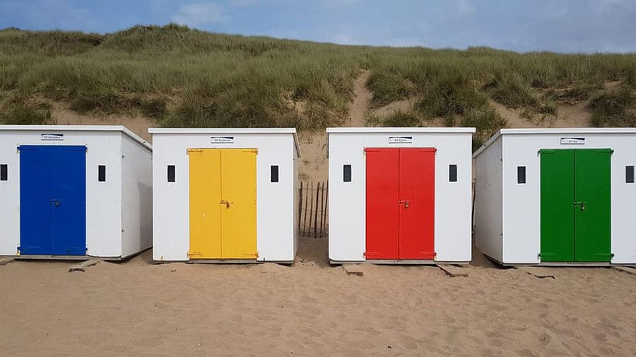 four white beach huts with blue, yellow, red and green doors with sand in front and dunes behind