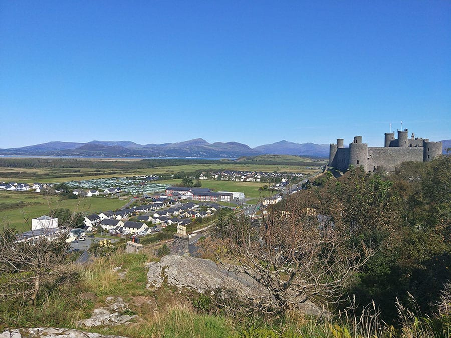 Castle on the right sitting above the town of Llandudno with hills behind