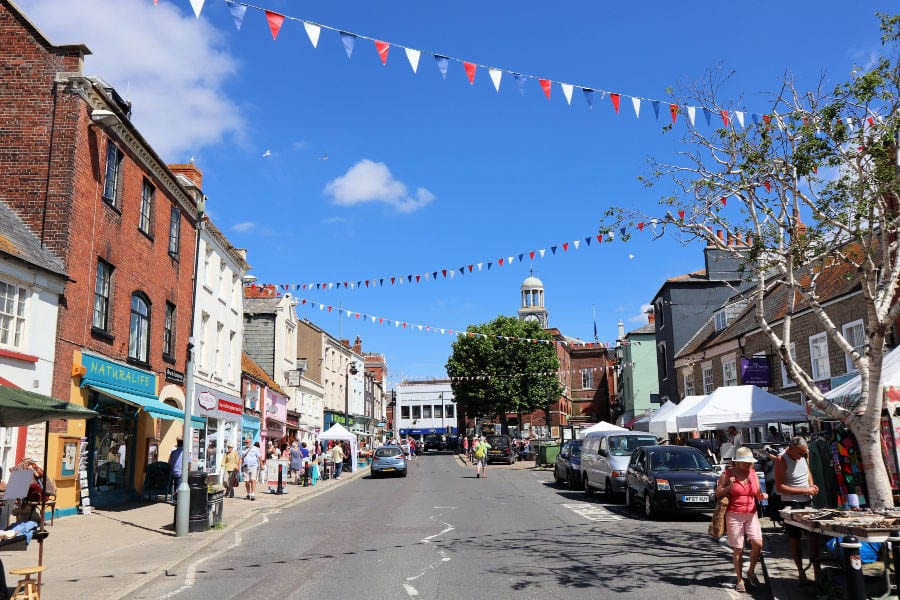 Bridport High Street with red, white and blue bunting and market stalls on the right