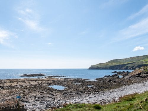 Pebble beach below Clifton Road in Port St Mary with hill filled with green fields in the background