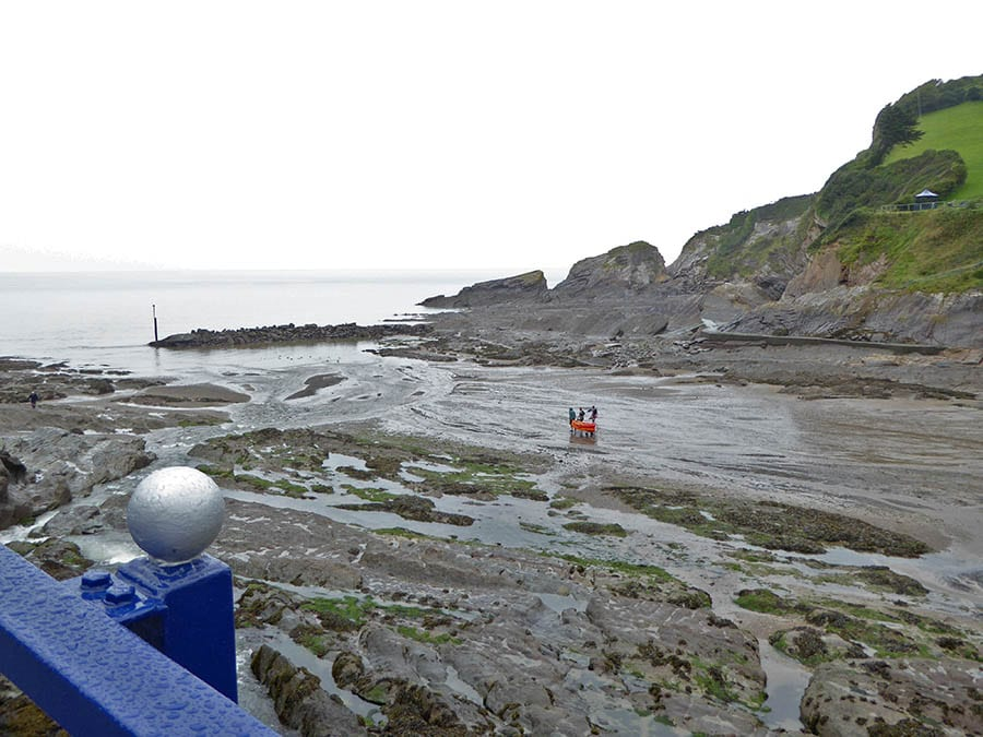 beach at Coombe Martin with tide out and 3 men taking an orange kayak out to sea