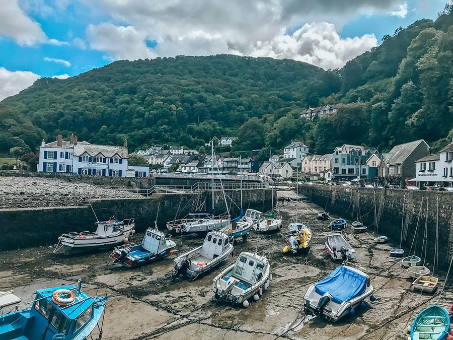 Lynton and Lynmouth harbour. The tide is out and the boats are resting on the ground. Thee are houses and mountains around