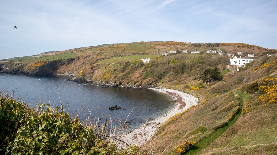 white pebble beach with green hill behind