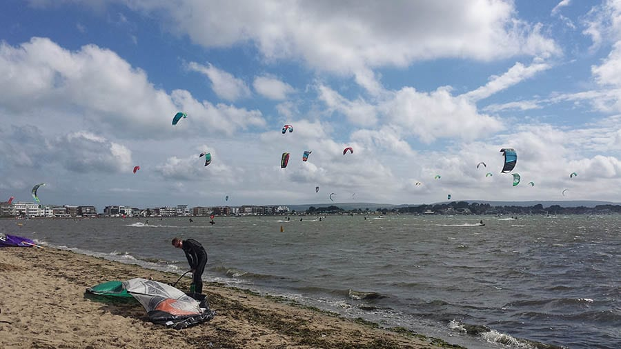 sky over Poole beach filled with kitesurfers