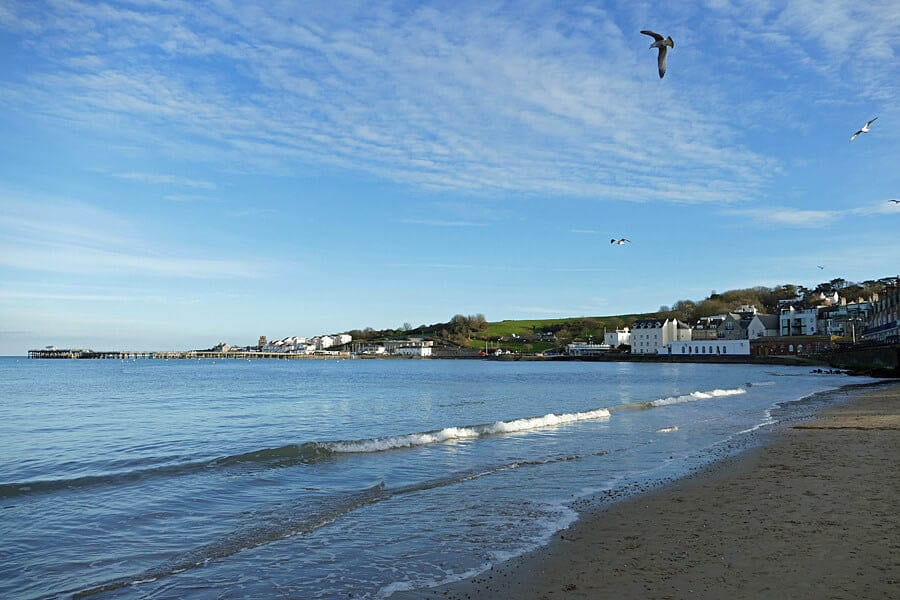 The beach at Swanage with the tide coming in and white houses in the background and blue skies.