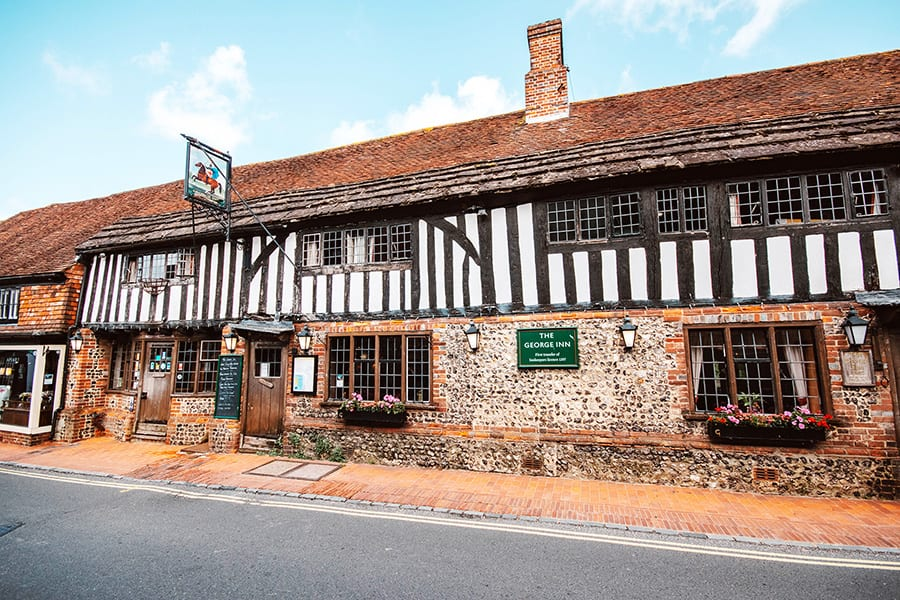 The George Inn, an oak beamed house with white render and black beams above stone walls
