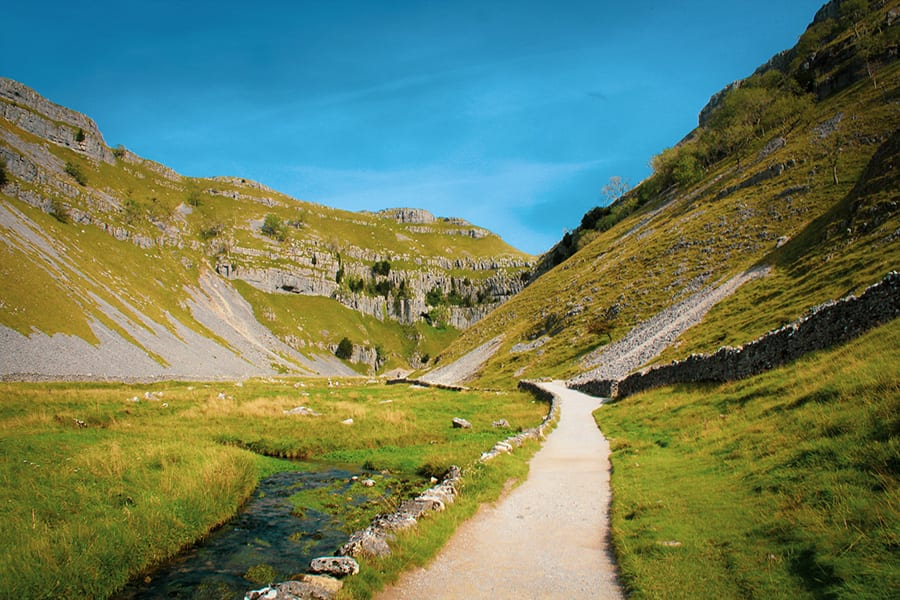 path leading through Gordale Scar with grass covered side and a burn running through it