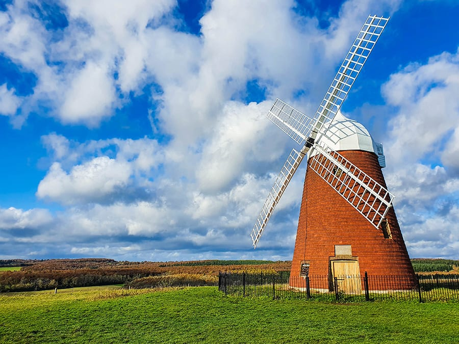 Halnaker Windmill, a red brick windmill with white top and white lattice sails surrounded by a black fence in a green field