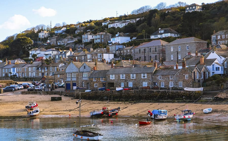 rows of houses going up a hill with a sandy beach in the foreground with boats on it
