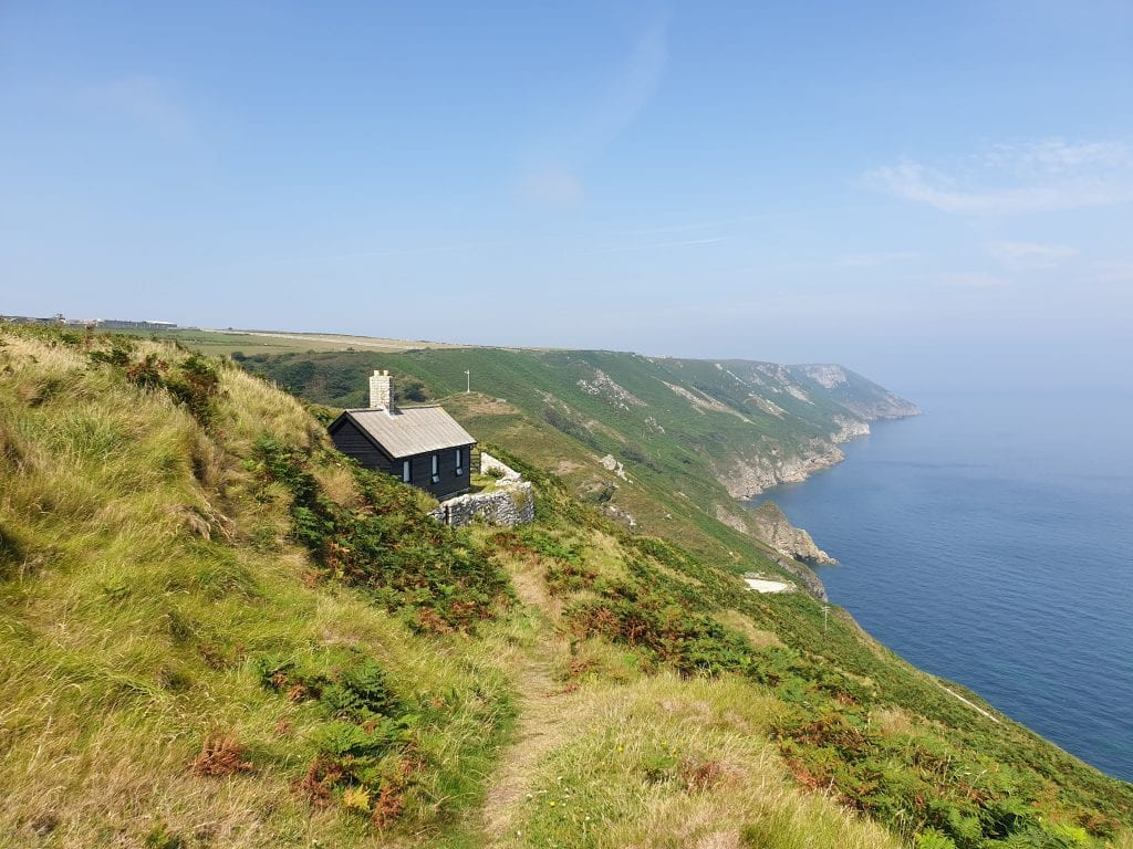 black wooden house sitting on the cliffside over looking the sea on Lundy Island