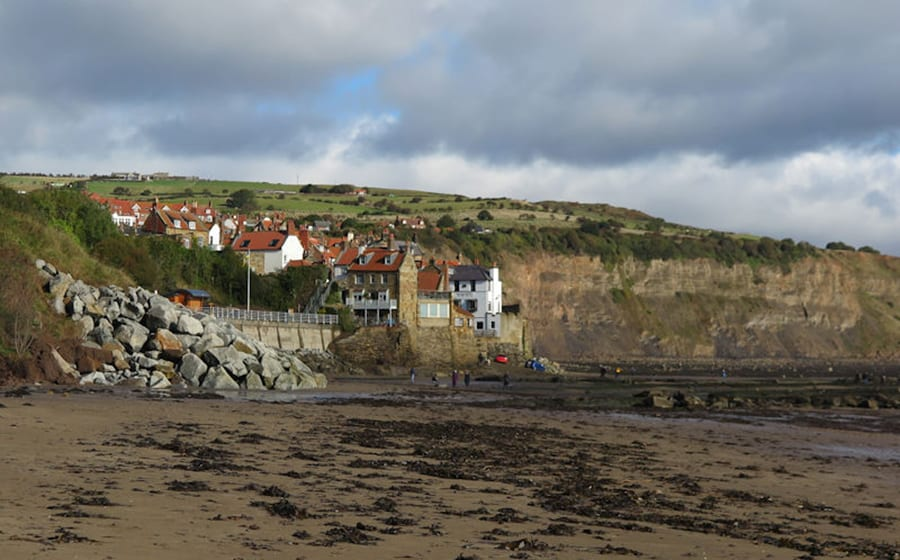 sandy beach with seaweed in the foreground and houses on the edge of a cliff in the background