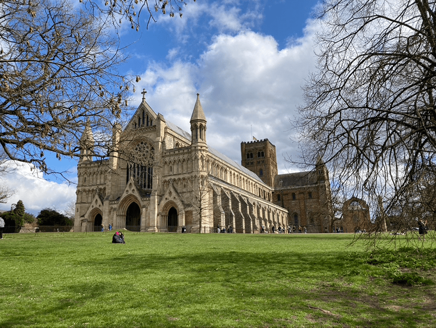 St Albans Cathedral with double buttresses and three arches entrances with stained glass windows above, one of the hidden gems in England