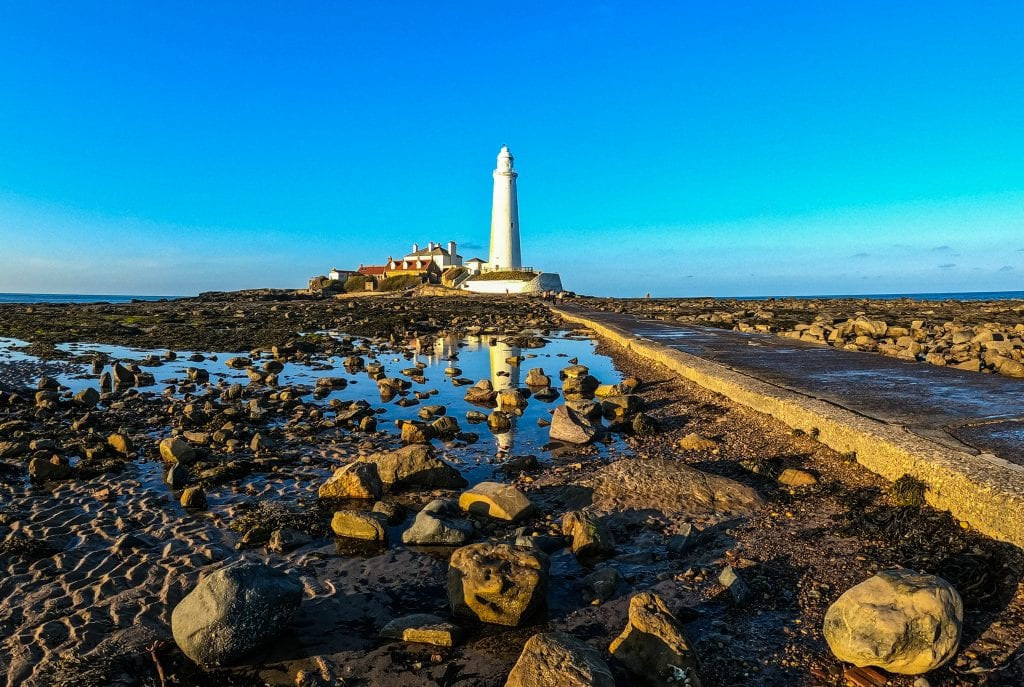 white light house with the tide out. A causeway divide the rocks and rockpools