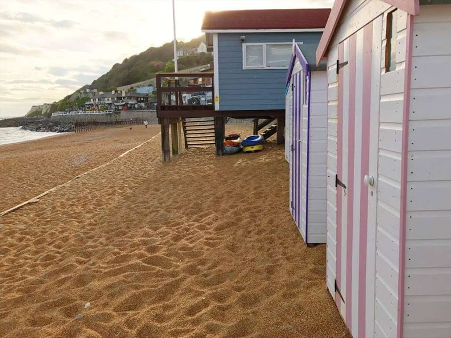 Sandy beach with painted beach huts, white with white and pink stripe door and white with white and purple stripe door