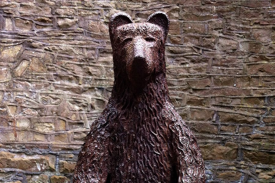 Statue of a bear with a stone wall behind