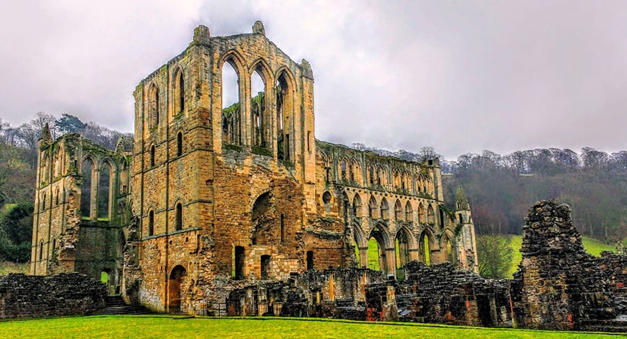 ruins of Rievaulx Abbey, a gothic abbey with arching empty windows