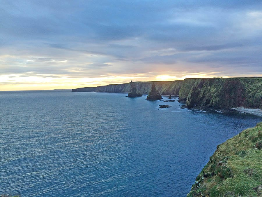 sea with view over grassy hills to Duncansby Stacks in the distance