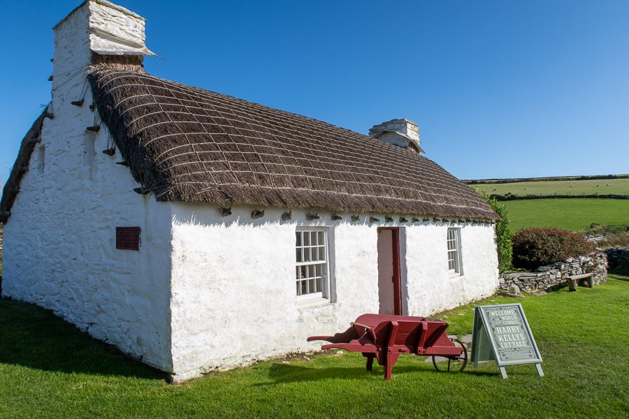 Typical Manx white stone cottage with thatched roof. There is a red painted wheelbarrow outside the door and a green painted sign