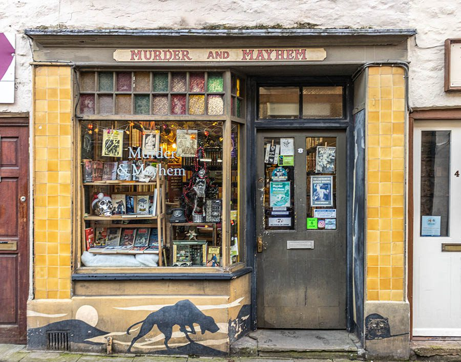 Front of bookshop called Murder and Mayhem with yellow tiles each side of the door, a mural of a hunting dog and a cat under the window.