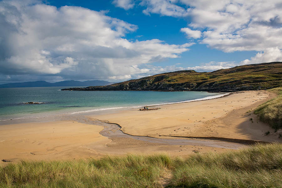 sandy beach with blue sea and green grass to the bottom and hills in the background
