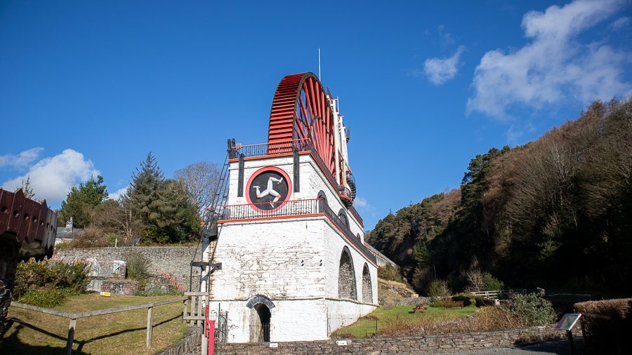 Large red waterwheel with white brickwork and Isle of Man three-legged man on the front