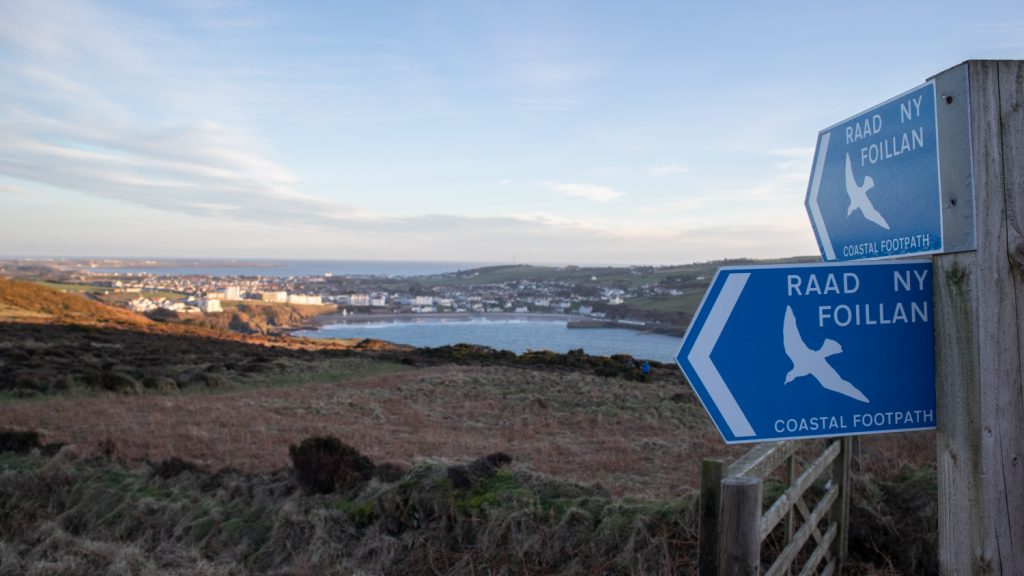 two blue signs saying Raad Ny Foillan with a bay in the background