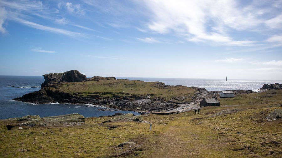 The Calf of Man with sea around it and a lighthouse in the background