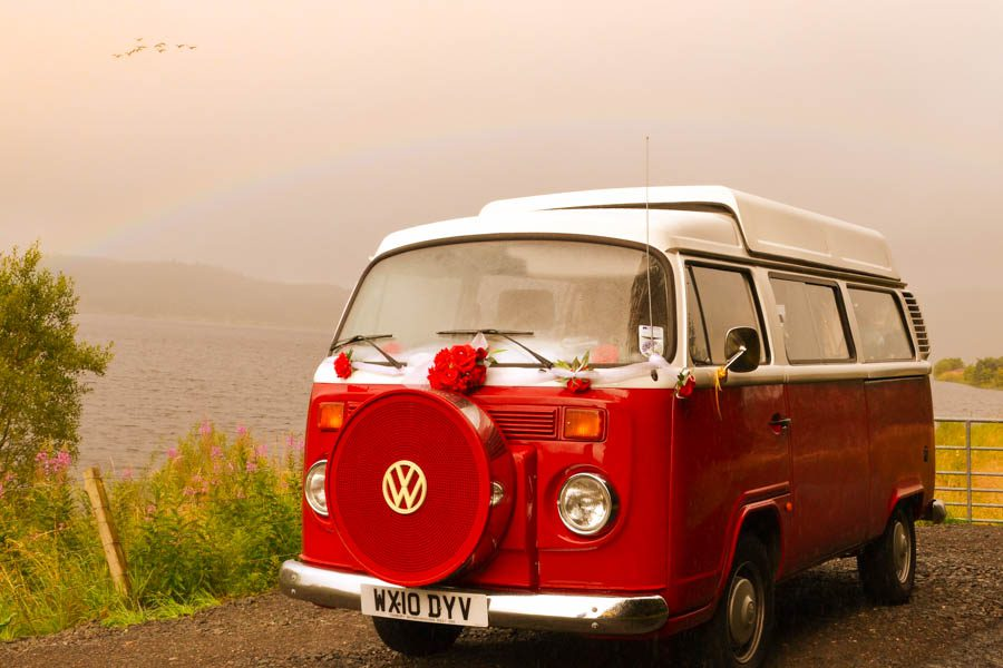 red vw camper vans with flower on the front and a loch in the background with a rainbow above