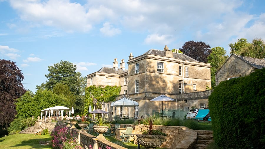 Exterior of the Burleigh Court Hotel, double fronted three storey hotel in creamy Cotswold stone with trees behind and grass in front