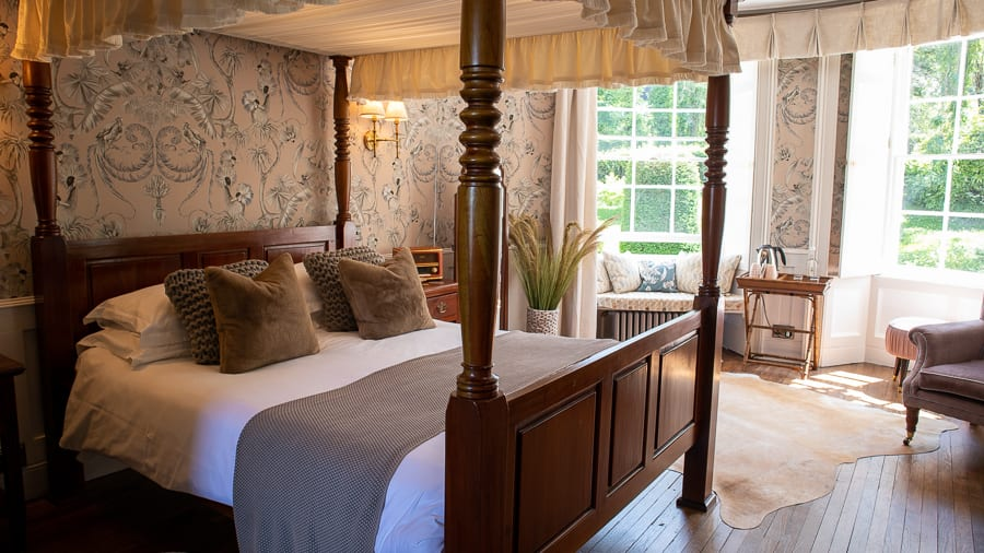 dark wood four-poster bed with mole coloured throw, caramel velvet cushions and pastel pink wallpaper with crested crane bird print in black, white and grey