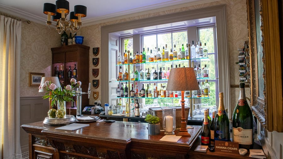 bar with bottles of alcohol on glass shelves on the window
