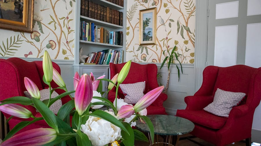 three red armchairs with pink lilies in the foreground