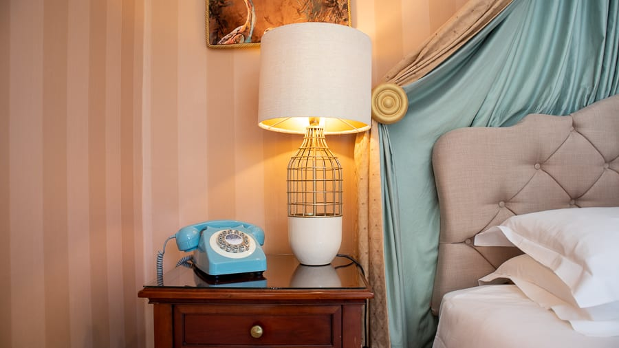 blue old fashioned dial phone next to lamp with open weave base and pale blue silk headboard